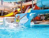 Child in bikini sliding water park. — Stock Photo