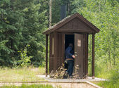 Woman entering restroom in forest — Photo