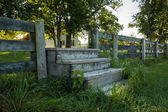 Steps through fence from field — Stock Photo