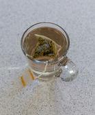 Chamomile teabag in glass mug on table — Stock Photo