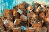 Old pile of rusty paint cans against wall — Stock Photo