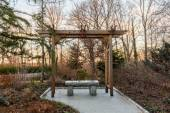 Wooden arbor in forest with stone seat — Stock Photo