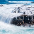 Постер, плакат: Raging sea flows over lave rocks on shore line