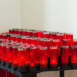 Rows of red votive candles in Catholic church — Stock Photo #66238373