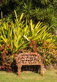 Tropical flowers overwhelm cast iron seat — Stock Photo