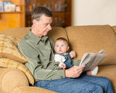 Young baby looking up at grandad with paper — Stock Photo