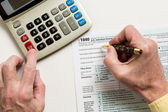Pen and calculator on 2014 form 1040 — Stock Photo