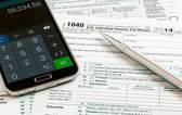 Pen and smartphone on 2014 form 1040 — Stock Photo