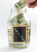 Hand inserting money into saving jar or bank — Stock Photo