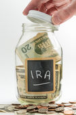Hand opening glass Jar used for IRA fund — Stock Photo