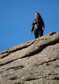Tourist climbs up the granite slopes of Haytor Rocks — Stock Photo