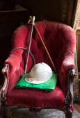 Riding silks and hat on red velvet chair — Stock Photo