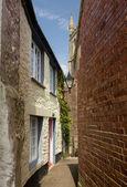 Narrow alley or street leading to parish church — Stock Photo