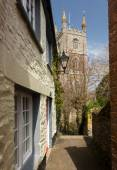Narrow alley or street leading to parish church — Stock Photo