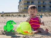 Baby girl tasting sand on beach — Stock Photo