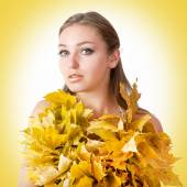 Beautiful woman with autumn leaves on yellow background. — Stock Photo