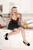 Beautiful young housewife in the kitchen. — Stock Photo