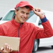 Delivery man with package outdoors — Stock Photo #51837421