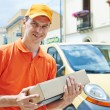 Delivery man with package outdoors — Stock Photo #51837535