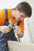 Carpenter works with hummer and chisel — Stock Photo