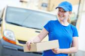 Delivery woman with package outdoors — Stock Photo