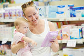 Woman with baby in shop — Stock Photo