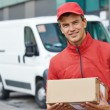 Delivery man with package outdoors — Stock Photo #52491179