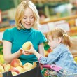 Woman and little girl shopping fruits — Stock Photo #52491485
