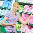 Woman choosing textile linen in shop — Stock Photo #52491509