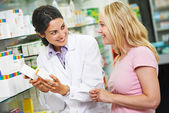 Pharmacy chemist and customer in drugstore — Stock Photo