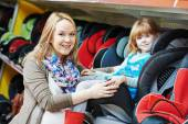Woman choosing car seat with child — Stock Photo