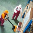 Worker with fork pallet truck — Stock Photo #53550147