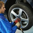 Auto mechanic screwing car wheel by wrench — Stock Photo #53556731