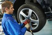 Auto mechanic screwing car wheel by wrench — Stockfoto