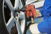 Auto mechanic screwing car wheel — Stock Photo