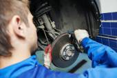 Auto mechanic at car brake shoes eximining — Stock Photo