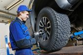 Auto mechanic screwing car wheel by wrench — ストック写真