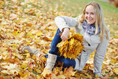 Woman with maple leaves at autumn — Stock Photo