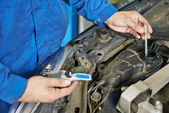 Auto mechanic tests car antifreeze liquid — Stock Photo