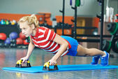 Woman pushing up in fitness gym — Stock Photo