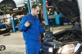 Mechanic checking oil level in automobile — Foto Stock