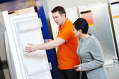 Shopping refrigerator with assistant — Stock Photo