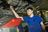 Auto mechanic disassembling axle — Stock Photo