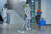 Worker cleaning floor with machine — Stock Photo
