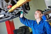 Auto mechanic at car suspension repairing — Stock Photo