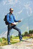 Tourist guide with map in mountains — Stock Photo