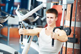 Man at chest pectoral exercises machine — Stock Photo
