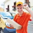 Delivery man with package outdoors — Stock Photo #67747407