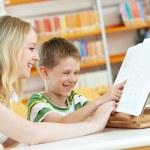 jovem mulher e menino lendo livro na biblioteca — Fotografia Stock  #67747477