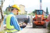 Builder engineer with laptop at construction site — Stock Photo